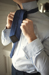 Man tying necktie in while standing at home - CAVF06337