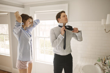 Couple getting dressed while standing by bathroom sink - CAVF06340