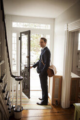 Man looking away while standing at doorway in home - CAVF06343