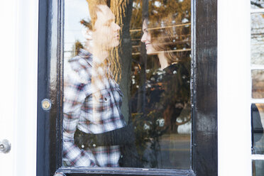Happy couple standing by window at home - CAVF06349