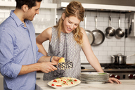 Woman looking at man grating cheese on pasta - CAVF06370