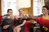 Happy friends toasting wineglasses while sitting on sofa - CAVF06373