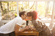 Couple kissing while sitting at table in home - CAVF06451