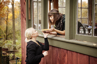 Woman giving tart to friend while leaning on window - CAVF06457