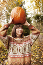 Woman looking up while carrying Halloween pumpkin - CAVF06460