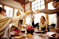 Friends raising celebratory toast at table in home - CAVF06466