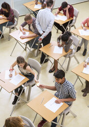 Overhead view of students passing note between desks during their GCSE exam - CAIF15220