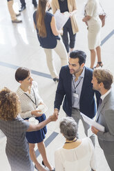 High angle view of group of business people shaking hands in office - CAIF15241