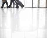 Business people walking in office with suitcases - CAIF15256