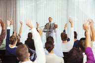 Businessman giving presentation in conference room, people raising hands - CAIF15265