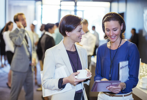 Portrait of two smiling women, talking in lobby of conference center during coffee break - CAIF15271