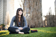 Woman looking away while sitting on grassy field - CAVF06562