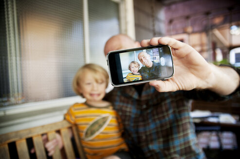 Happy family taking selfie while sitting on swing at home - CAVF06574