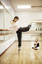Girl looking at teacher dancing while sitting on floor - CAVF06586