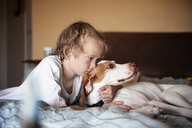 Boy embracing dog while lying on bed at home - CAVF06748