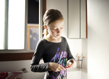 Girl putting toothpaste on toothbrush in bathroom - CAVF06778