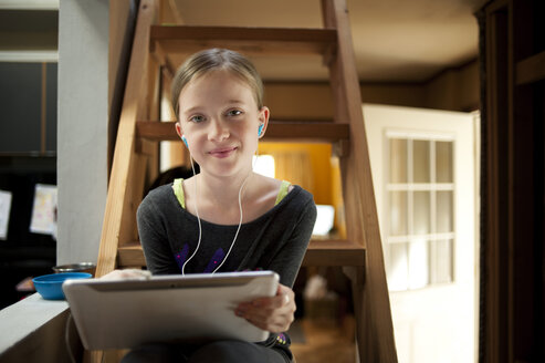 Portrait of girl listening music while using tablet computer on ladder at home - CAVF06781