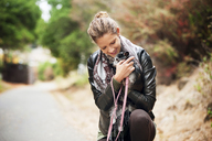 Happy woman embracing dog on road - CAVF06811
