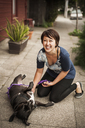 Portrait of woman playing with dog on footpath - CAVF06853