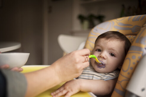 Cropped image of mother's hand feeding baby boy at home - CAVF06907