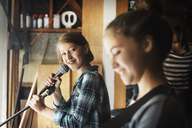Girl looking at friend while singing in recording studio - CAVF06934