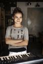 Girl standing by piano in recording studio - CAVF06937