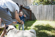 Happy family with dog playing in backyard - CAVF06955