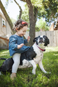Happy baby girl sitting on dog in backyard - CAVF06961