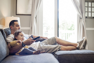 Father and daughter watching television at home - CAVF06964