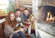 Friends celebrating with drinks in log cabin - CAIF15292