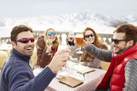 Friends celebrating with drinks in the snow - CAIF15307
