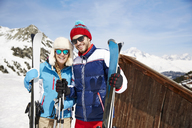 Couple holding skis on mountain together - CAIF15313