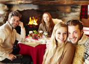 Friends eating together by fireplace - CAIF15316