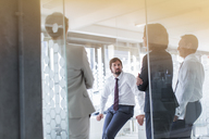 People having meeting in modern office seen through glass door - CAIF15361