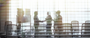 Business people standing in conference room shaking hands - CAIF15418