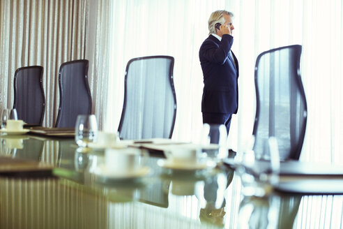 Businessman looking out of window and using mobile phone in conference room - CAIF15436