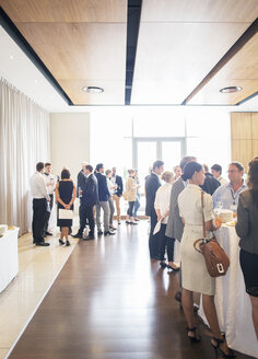 Large group of people socializing in lobby of conference center during coffee break - CAIF15469