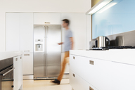 Man walking towards refrigerator in his modern kitchen - CAIF15514