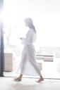 Woman wearing white bathrobe walking through modern corridor with mobile phone - CAIF15517