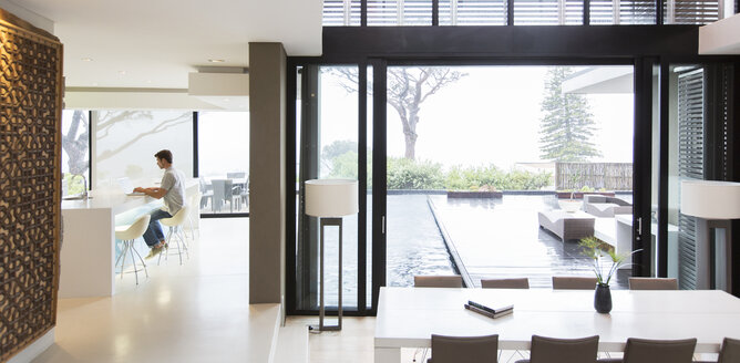 Young man using laptop in modern kitchen, dining area with patio door and swimming pool in foreground - CAIF15520