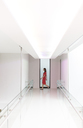Woman in red dress walking through white modern corridor - CAIF15532
