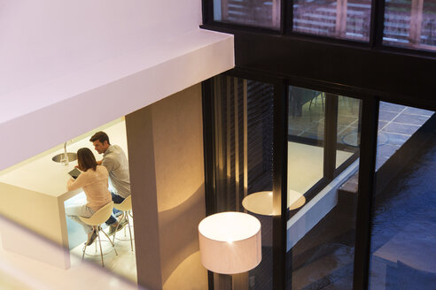 Elevated view of couple using tablet pc in dining room - CAIF15547