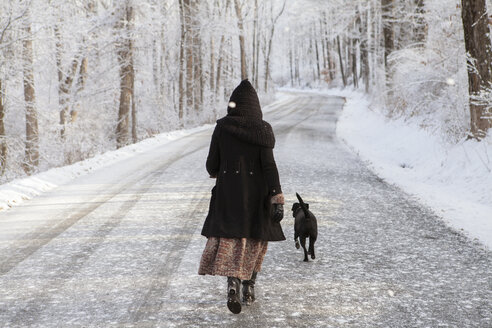 Rear view of woman walking with dog on road during winter - CAVF06979