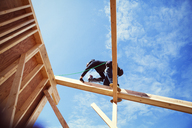 Low angle view of worker making construction frame against blue sky - CAVF07006