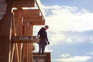 Worker standing on wooden frame against sky during sunny day - CAVF07015