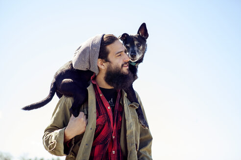 Thoughtful man carrying dog on shoulders while standing against clear sky - CAVF07021