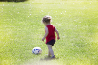 Rear view of girl playing soccer on grassy field - CAVF07036