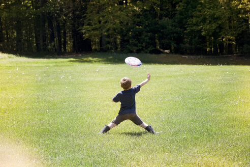 Rear view of boy throwing frisbee at park - CAVF07048