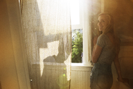 Woman standing by window at home - CAVF07075