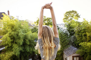 Rear view of woman stretching while sitting on roof - CAVF07081
